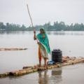 Woman steering a raft in deep flood water in Bangladesh