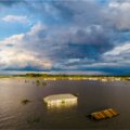 Landscape image of large flood with the roof of a house visible in the middle