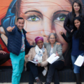 A group of people pose in front of street art