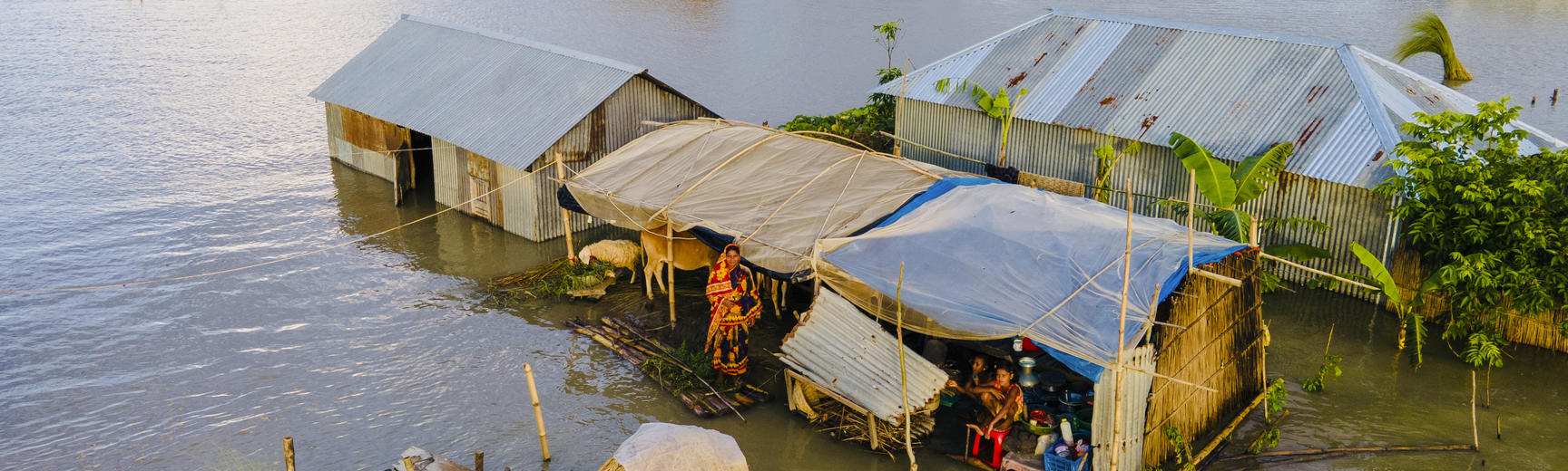 Image of houses stranded in flood water with people inside