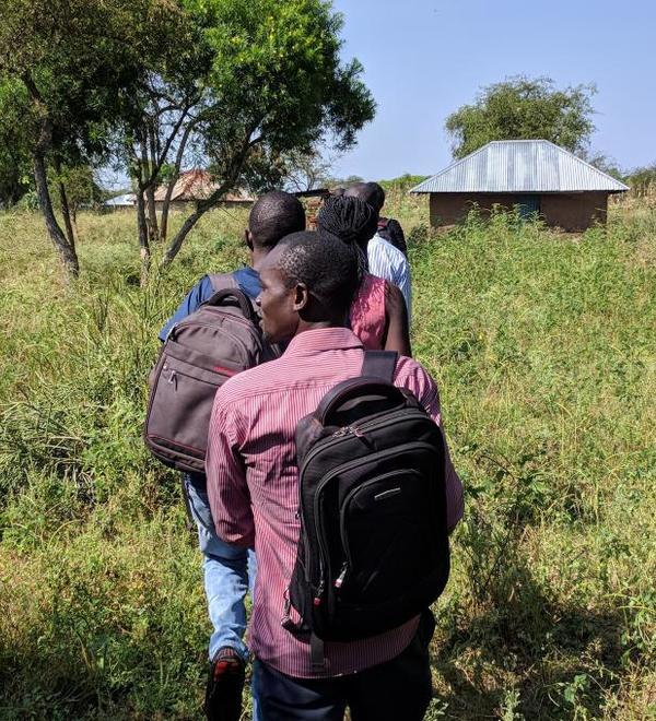 Men walking in a line through grass in Siaya Kenya